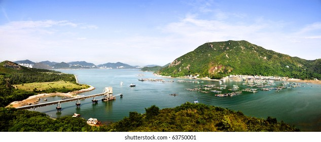 Peaceful fishing village on the shore with green mountains in the background and a clear blue sky.
