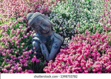 Peaceful garden. Traditional serene buddha statue ornament with beautiful flowers. Mindful serenity and nature in this calming image portraying tranquility and mindfulness in zen meditation.