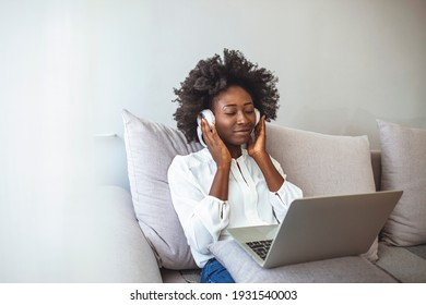 Peaceful girl in modern wireless headphones sit relax on comfortable couch listening to music, happy calm young woman in earphones rest on cozy sofa, enjoy good quality sound, stress free concept