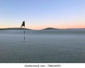 Peaceful golf court in morning sun with cold white frost over grass.