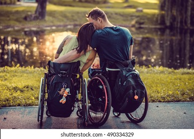 Peaceful handicapped young couple in wheelchairs in autumn park. View from the back.