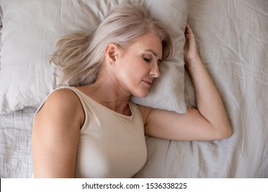 Peaceful healthy beautiful 50s mature woman lying asleep on comfortable pillow orthopedic mattress sleeping well in cozy bed alone, calm serene old female resting in bedroom, close up top view
