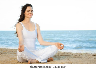 Peaceful healthy & fit young woman meditating on the beach