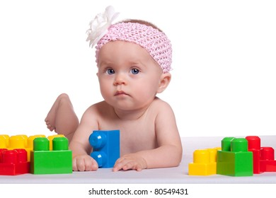 A peaceful image of an infant playing with plastic blocks.