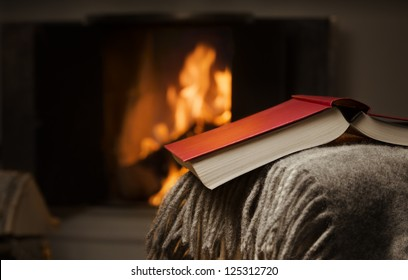 Peaceful image of open book resting on a arm rest of a couch. Warm fireplace on background.