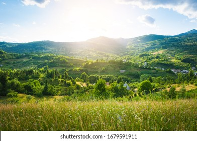 A peaceful landscape, green hills in spring time. A country road is cutting through the immaculate grass, illustrating the idea of travel , tourism or exploring