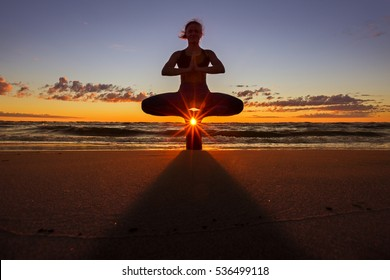 Peaceful landscape with a young woman in the beach at sunset practicing yoga - sitting in a lotus position on a small stump.