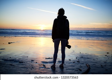 Peaceful lifestyle photograph of silhouette of woman photographer standing in sand on beach with camera looking out at ocean watching the sunset