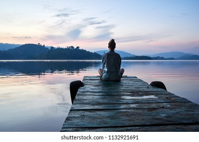 Peaceful lifestyle shot of woman sitting on dock at sunset on Lake Bunyonyi, Uganda, Africa. - Shutterstock ID 1132921691