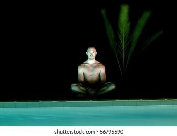 peaceful man doing yoga at night at pool
