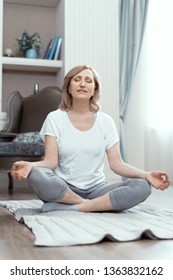 Peaceful Mature Woman Sits With Her Legs Crossed In Yoga Pose. Beautiful Woman Sits In Lotus Position Meditating