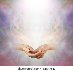 Peaceful Meditation - a pair of female gently cupped hands with a shaft of white light above on a misty ethereal wispy background providing plenty of copy space