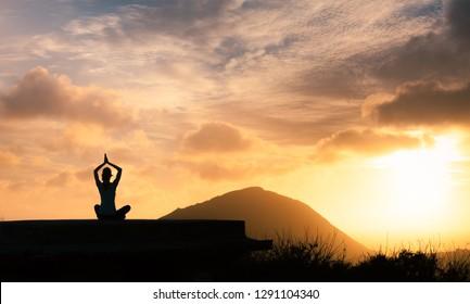 Peaceful meditation at sunset.  Woman meditating.