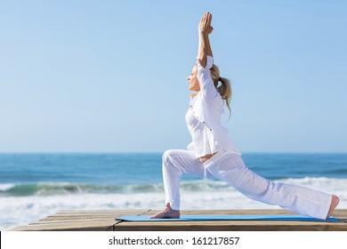 peaceful mid age woman doing yoga exercise on beach