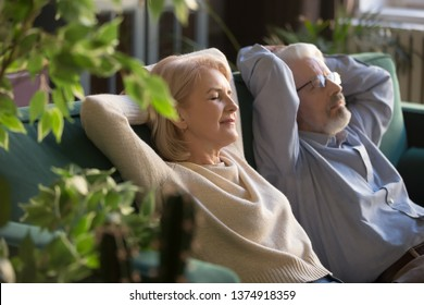 Peaceful middle aged man and woman with closed eyes relaxing on comfortable couch at home, mature family daydreaming together, grey haired wife and husband resting with hands behind head, breathing
