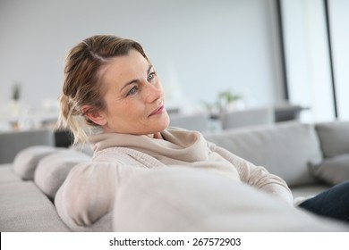 Peaceful middle-aged woman sitting in sofa