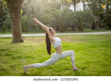 Peaceful mind and healthy body Concept. Sporty young yoga woman practising yoga balancing in a warrior asana at the local park at sunny summer day.