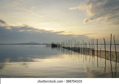 Peaceful morning at the beach with some poles holding net leading into the sea