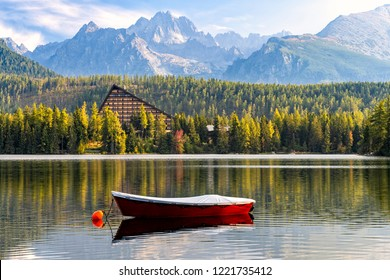 Peaceful mountain scene with mountain hotel next to a lake with boat. Scenic view of Strbske Pleso, High Tatras National Park, Slovakia. Focus on a boat in front.