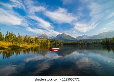 Peaceful mountain scene with mountain hotel next to a lake with boat. Scenic view of Strbske Pleso, High Tatras National Park, Slovakia.