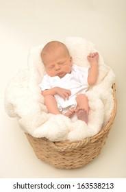 peaceful newborn baby or infant sleeping in basket