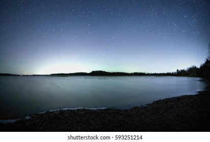 Peaceful night scene with starry sky at a lake in Finland. Reflection of stars on the still water of the lake.