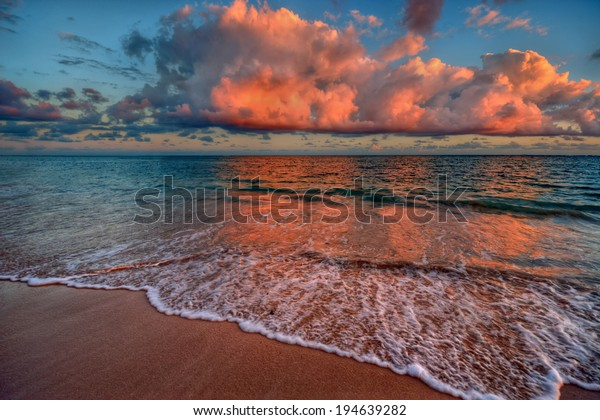 Peaceful ocean sunset with crimson clouds and sandy beach