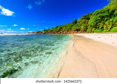 Peaceful perfect postcard of Seychelles beach in La Digue. The white sandy beach and turquoise sea of Anse Cocos can be reached with a trek starting from Grand Anse and passing through Petite Anse.