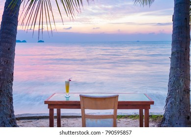 Peaceful place have tropical cocktail, table, chair on beach to see beautiful sunset for relax time at Samui island, Thailand (long exposure)