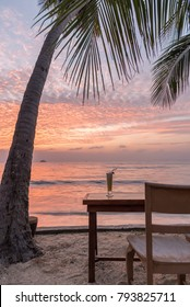 Peaceful place have tropical cocktail, table, chair on beach to see beautiful sunset for relax time at Samui island, Thailand