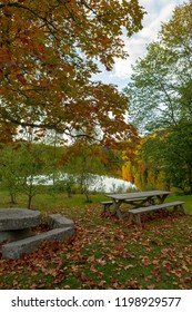 Peaceful place for a picnic. Wooden table in the park, reflecting lake, colorful forest. Autumnal scenery in Finland.