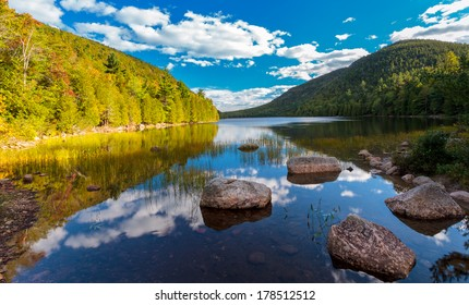 peaceful pond in Acadia national park, blue cloudy skies and morning light