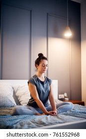 Peaceful pretty middle aged active woman practising yoga on the bed holding eyes closed, sitting in Half Lotus exercise, Ardha Padmasana pose and wearing sportswear at night.