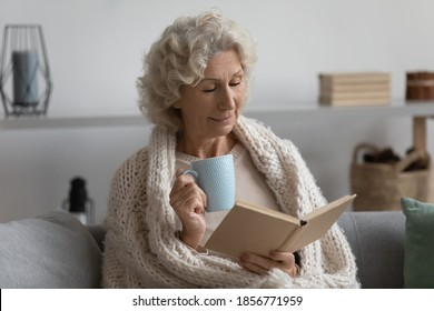 Peaceful satisfied mature woman wrapped warm blanket reading book, favorite literature and drinking tea or coffee, happy middle aged senior female relaxing, enjoying free time, weekend at home