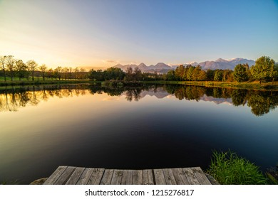 Peaceful scene of beautiful autumn mountain landscape with lake, colorful trees and high peaks. Colorful autumn foliage casts its reflection on the calm waters during sunset.