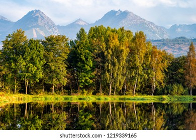 Peaceful scene of beautiful autumn mountain landscape with lake, colorful trees and high peaks in High Tatras, Slovakia.