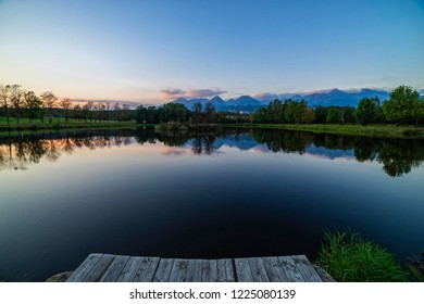 Peaceful scene of beautiful autumn mountain landscape with lake, colorful trees and high peaks during sunset blue hour.
