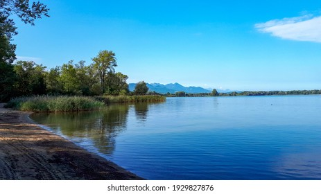 Peaceful scene at lake Chiemsee with blue clear sky and mountains in the background. Panoramic view of the beach of lake Chiemsee in summer