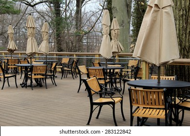 Peaceful scene of wood table and chairs with big, shade umbrellas, set on outdoor patio in wooded area, ready to make guests feel welcome, once restaurant opens for business.