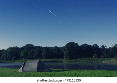 A peaceful scenery, lit by the full moon, overseeing the forest with a tent by the river and the star trails in the night sky counting the passage of time