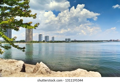 Peaceful scenic view of riverbank with high rise buildings and white clouds on blue sky