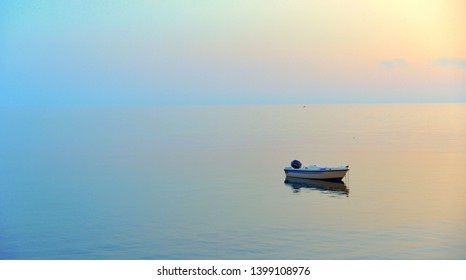 a peaceful sea with warm sunset colors and a solitary boat in a beach near Agrigento in Sicily Italy