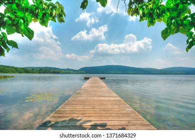Peaceful serene pier leading out into Rockland lake in Congers New York. The leading lines take you away into this peaceful upstate getaway. Nature's beauty is in full swing.