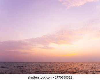 Peaceful serene sea scape and golden purple tone sunset or sunrise sky with clouds, tropical island ocean view at dawn or dusk