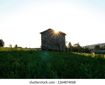 Peaceful, solitary stone hut on a meadow at sunrise