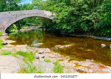 Peaceful summer day watching the clear water of the River Ribble flow under an old stone bridge near Stainforth.
