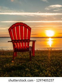 Peaceful sunset and a beach chair overlook the stunning Lake Minnehaha in Clermont, FL.