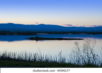Peaceful twilight scene at the Sacramento National Wildlife Refuge in the California Central Valley with distant blue mountains and a few small pink and gray clouds on the horizon