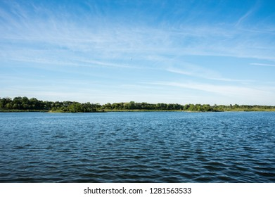 Peaceful, uncultivated landscape under a blue sky at Whalon Lake nature area in Bolingbrook, Illinois