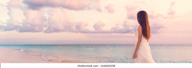Peaceful vacation paradise woman walking on sunset beach with pastel colors sky and ocean for tranquility and serenity banner. Girl in white wedding dress relaxing on luxury tropical summer getaway.